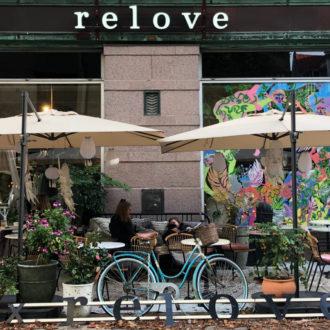 Dos grandes sombrillas protegen del sol las mesas de la terraza de un café ante un edificio de piedra con altos ventanales.