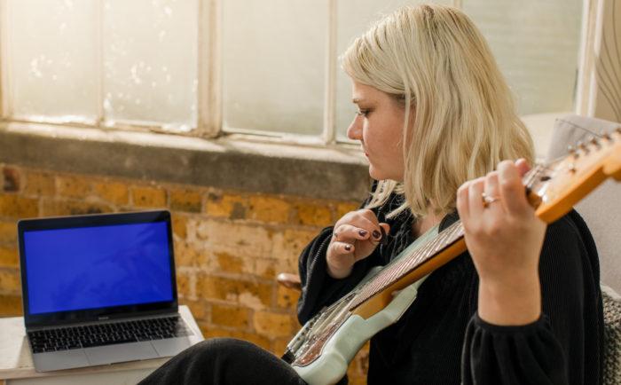 Uma mulher toca violão enquanto olha para um laptop na mesa ao lado dela.