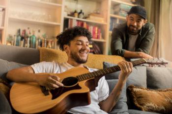 Um homem sorridente se senta em um sofá e toca violão, enquanto outro homem escuta.