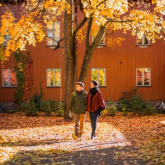 A man and a woman walking in front of red wooden houses and a fall foliage coloured tree and leaves