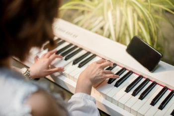 Человек играет на пианино, глядя в смартфон, стоящий на пианино.