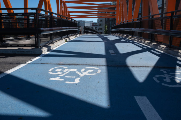 A stencil picture of a bicycle decorates the pavement of a bridge made out of girders.