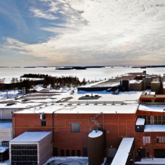 Under a covering of snow, a long brick building stretches out beside a bay, with islands visible in the distance.