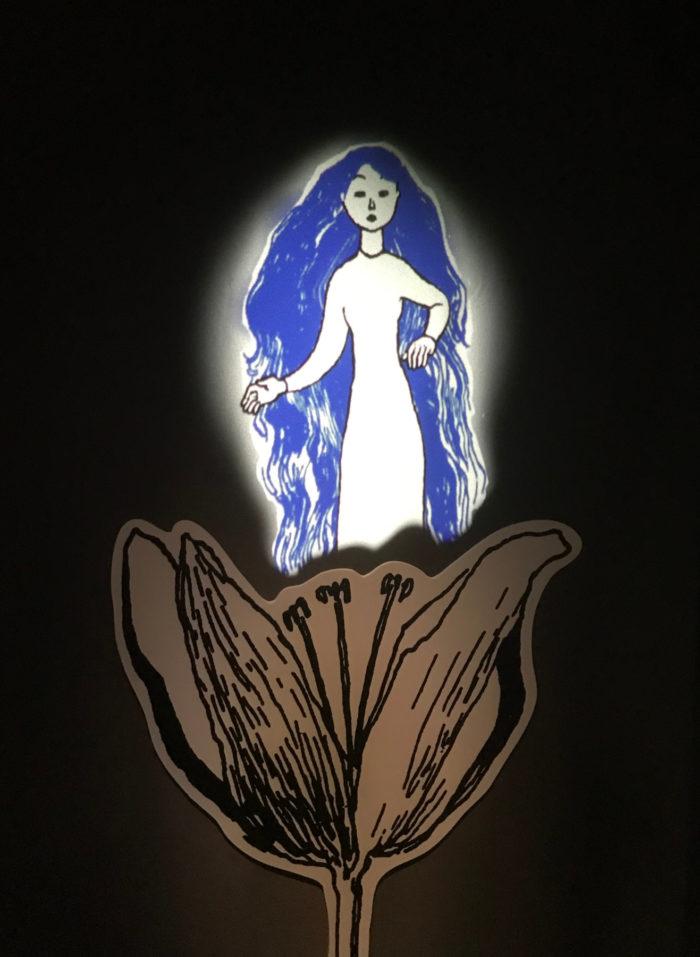 一幅画,画上的长发女子站在一朵花里。