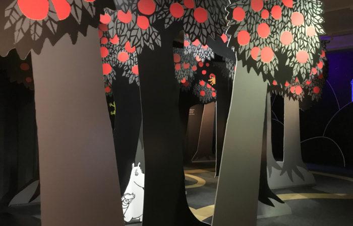 Uma floresta de árvores bidimensionais com um personagem Moomin atrás de uma delas.