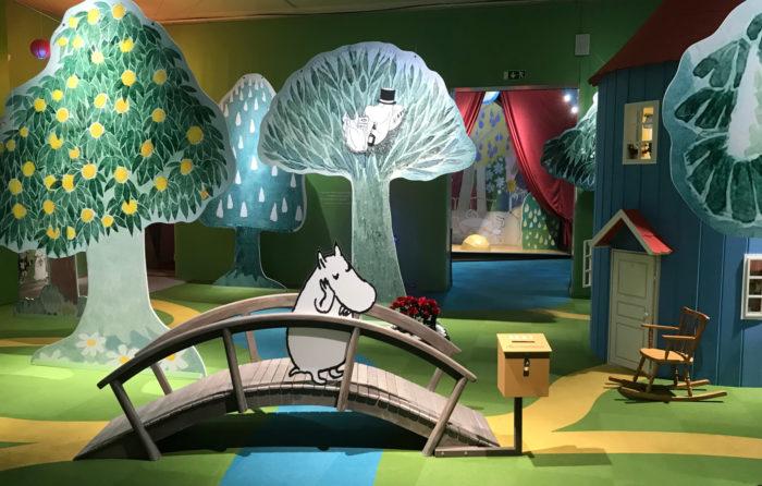Um personagem Moomin espera em uma ponte em uma cena que inclui vários cenários dos livros.