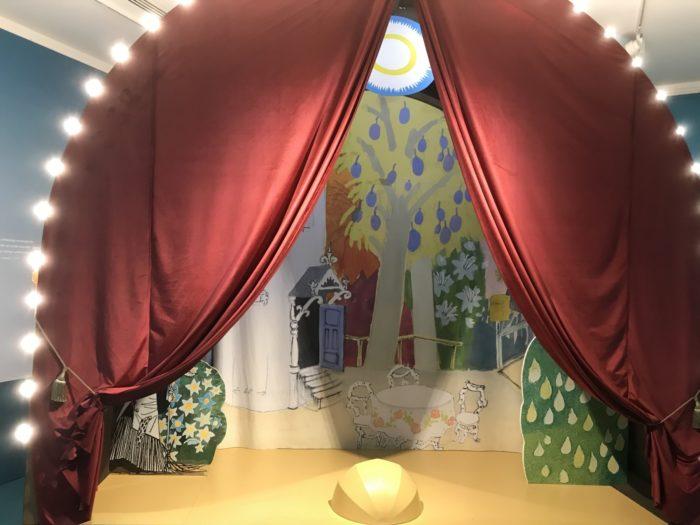 一座小舞台的两侧装点着帘幕和灯。