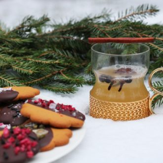 A plate of gingerbread cookies, a spruce branch and a drink cup are placed on a layer of snow.