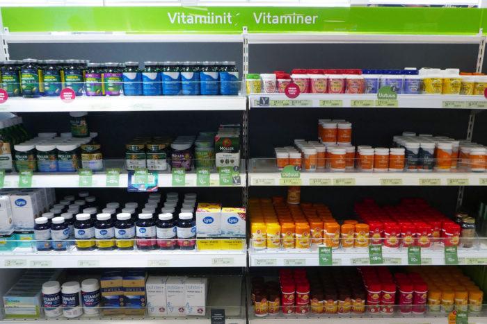 Банки с витаминами на полках. Сверху надпись «витамины» на финском и шведском.