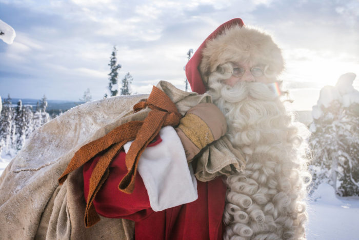 Santa Claus carries a bag over his shoulder, with a snowy forest in the background.