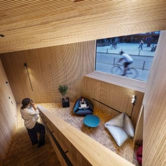 Mulher se senta em uma poltrona com um laptop, em um espaço onde as paredes, tetos e escadas são todos feitos de madeira.
