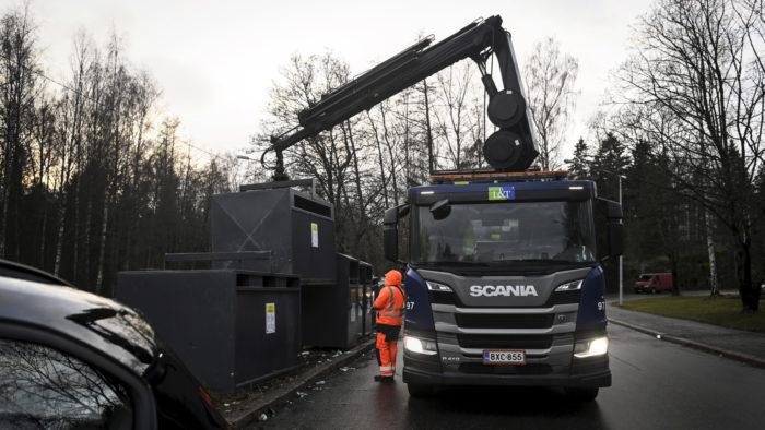 Рабочий стоит рядом с грузовиком и большими баками для мусора.
