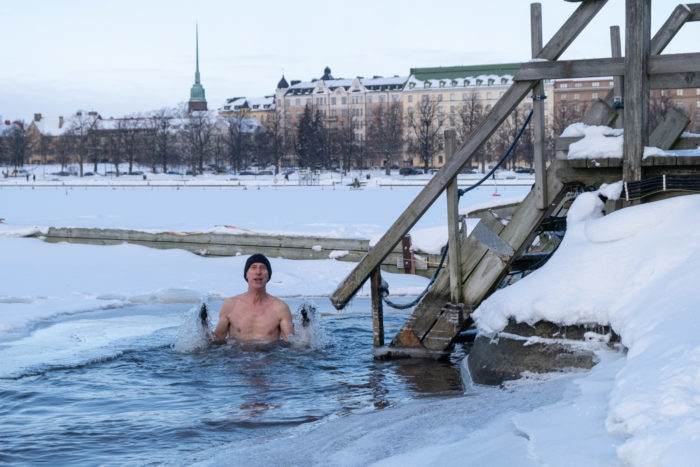 A man is up to his chest in water in a large hole in the snow-covered sea ice, with an exit ladder nearby and a view of Helsinki in the background.