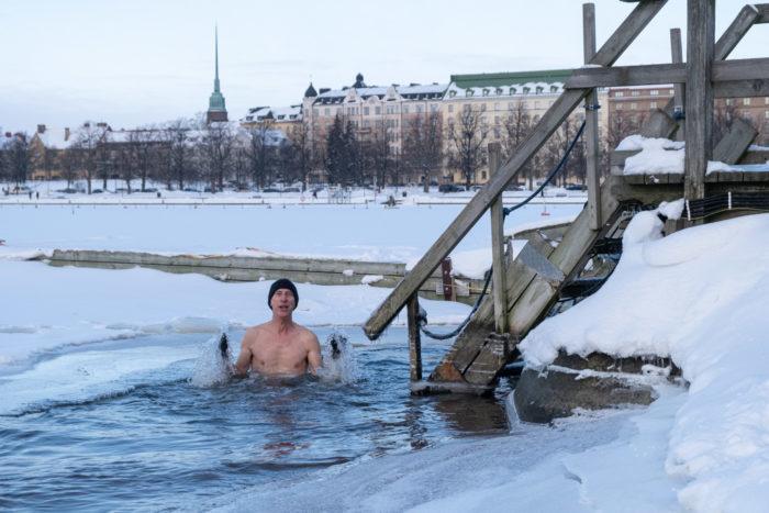 Мужчина по грудь в воде обширной полыньи на заснеженном льду моря, рядом – ступеньки для спуска в воду, на заднем плане открывается вид на Хельсинки.