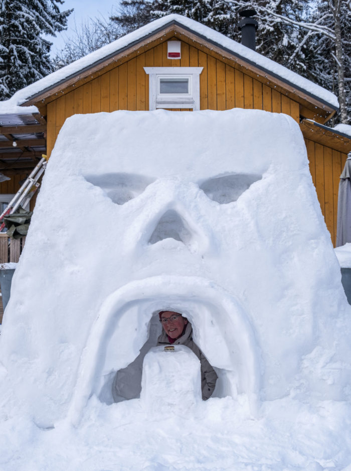 A person looks out of a window in a snow fort that has been made to resemble an angry face.