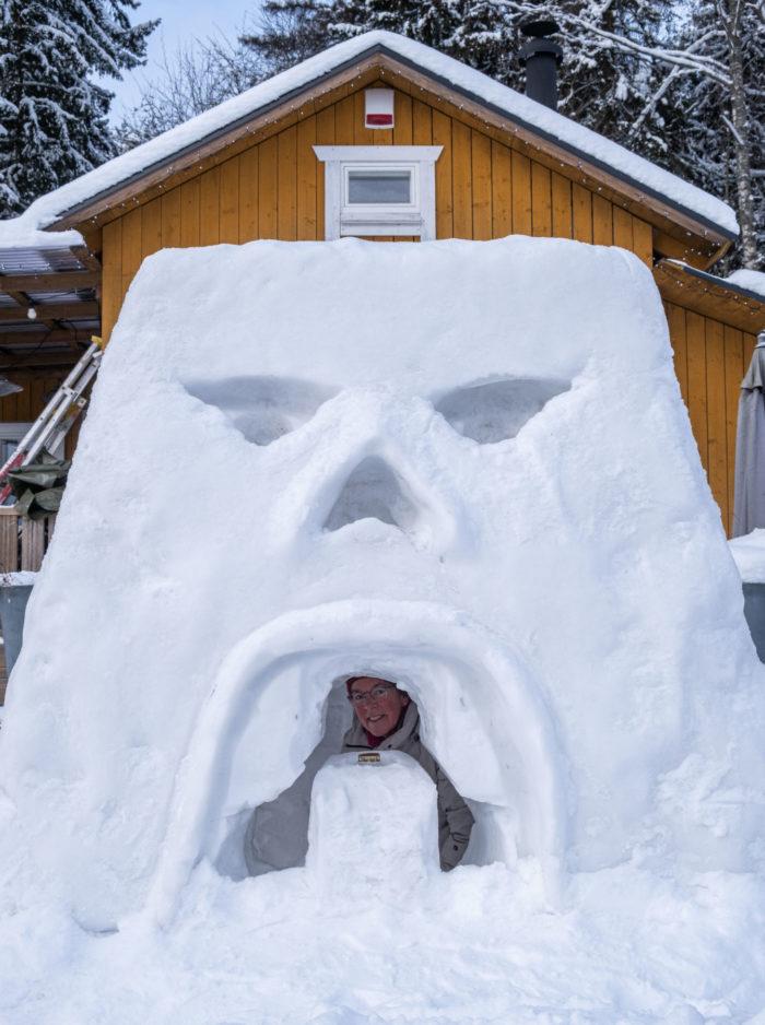 Человек смотрит из окна снежного форта, который выполнен в виде грозного лица.