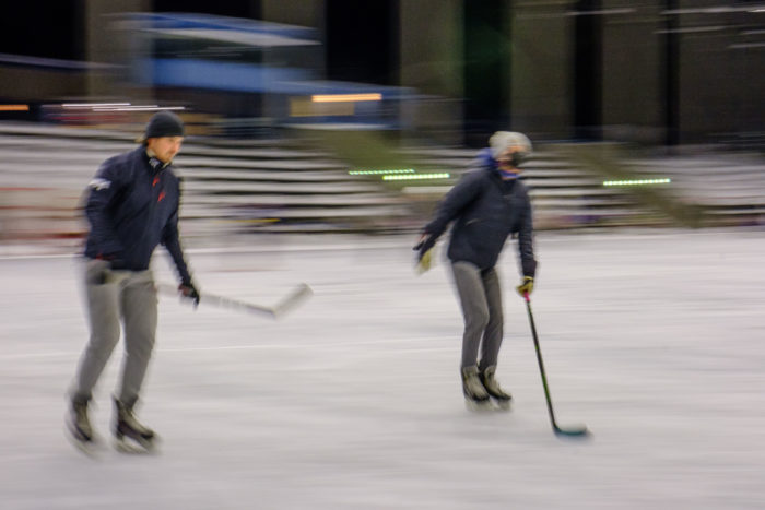 Two ice hockey players skate past on an outdoor rink.