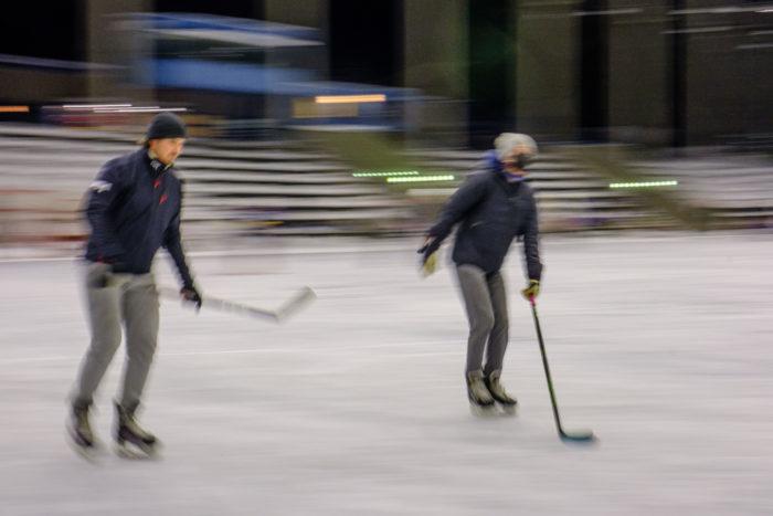 Два хоккеиста с клюшками на открытом катке.