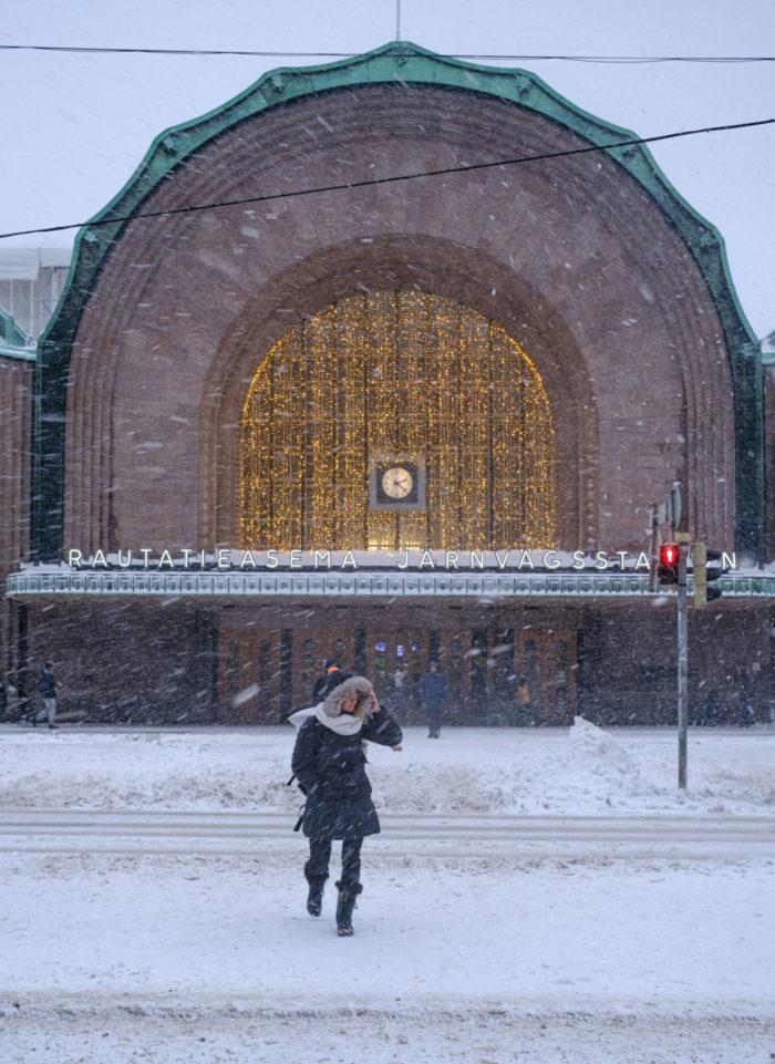 Человек пересекает улицу перед зданием во время снежного бурана.