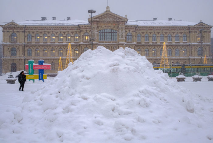 A stately museum building is partially visible behind an enormous pile of snow.
