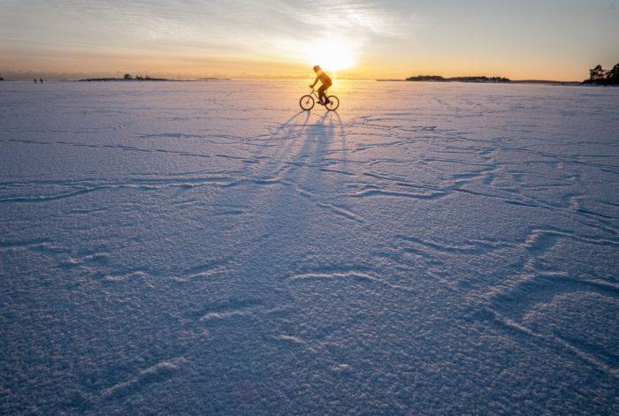 Велосипедист едет по равнине обширного заснеженного пространства.