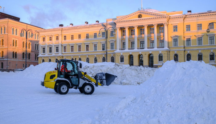 An earthmoving machine piles snow into mounds in front of a government building.