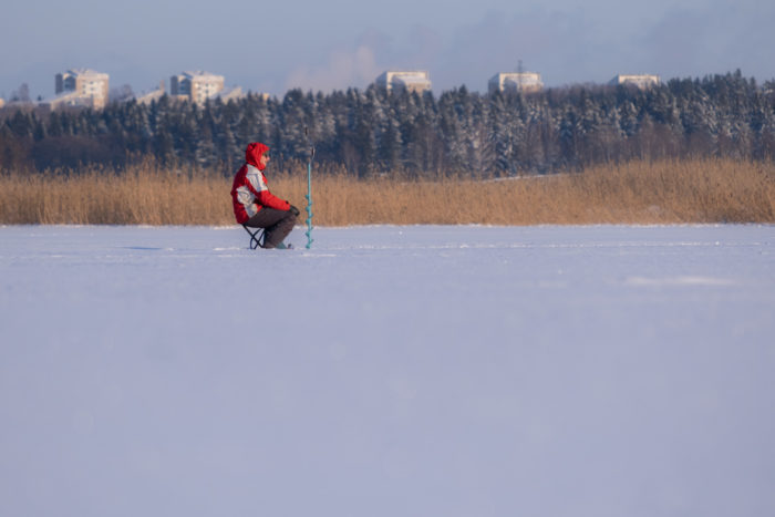 A person sits on a stool in the middle of a frozen bay, with apartment buildings in the background.