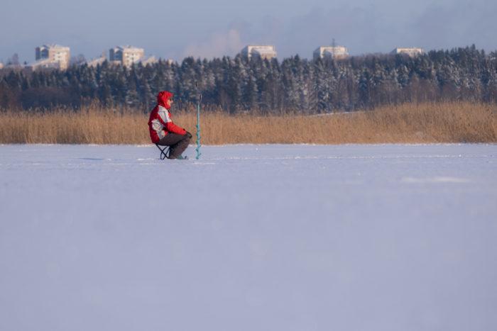 Человек сидит на табурете посреди замерзшей бухты на фоне жилых домов.