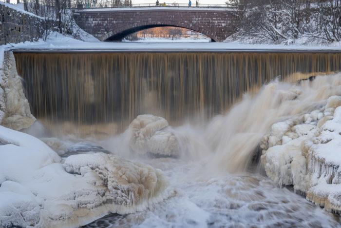 Люди на мосту смотрят на водопад и ледовые образования перед ним.