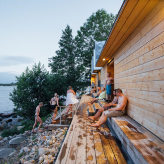 Several people sit, wrapped in towels, on a wooden bench outside a sauna on a rocky shore.