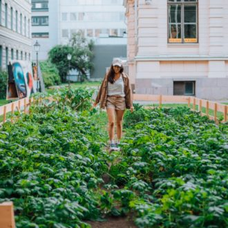 A woman stands in the middle of an urban garden plot.