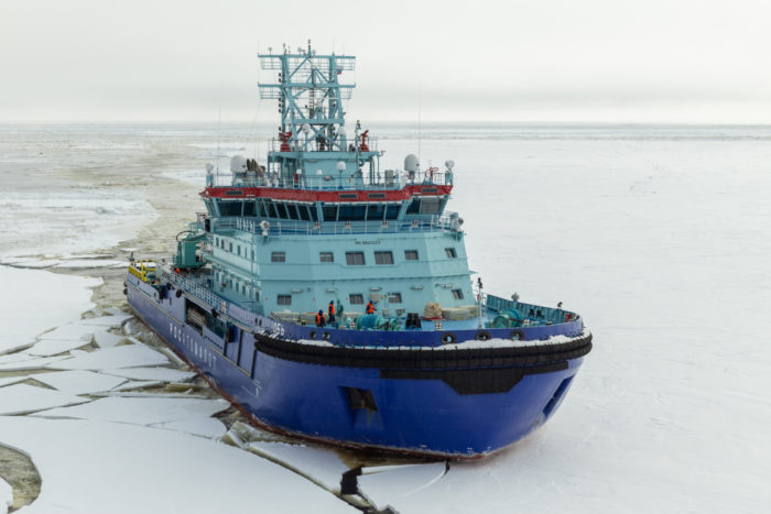 A ship moves through ice cover, leaving chunks of ice floating on the water.
