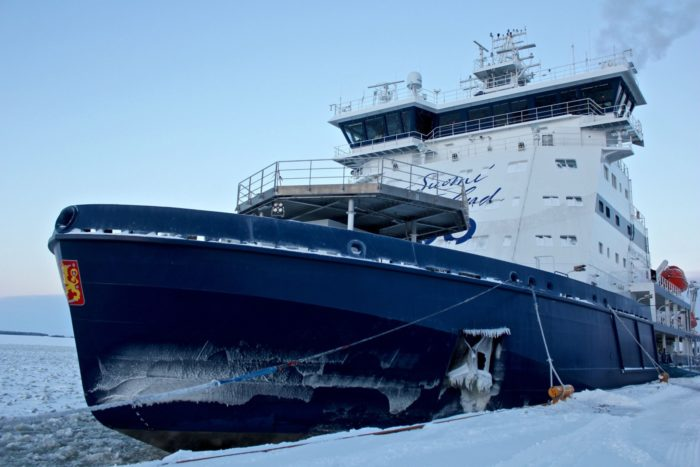 A blue and white ship rests in front of an ice-covered sea.