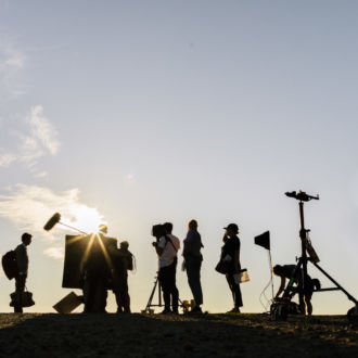 Silhouettes of people and camera equipment are next to a ship.