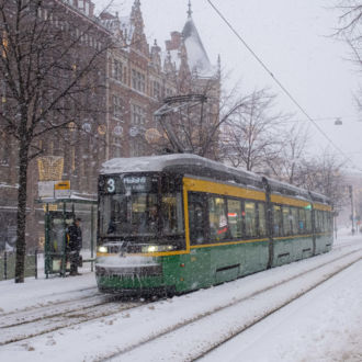 Snow falls as a tram progresses down a snow-covered street.