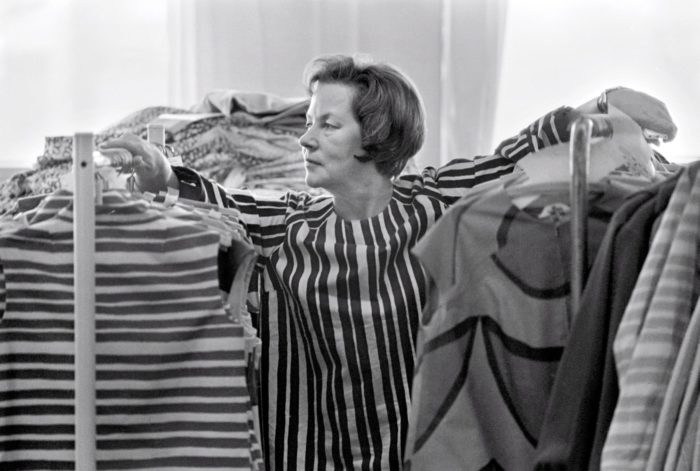 A woman in a striped blouse stands between two racks of similarly striped clothing.