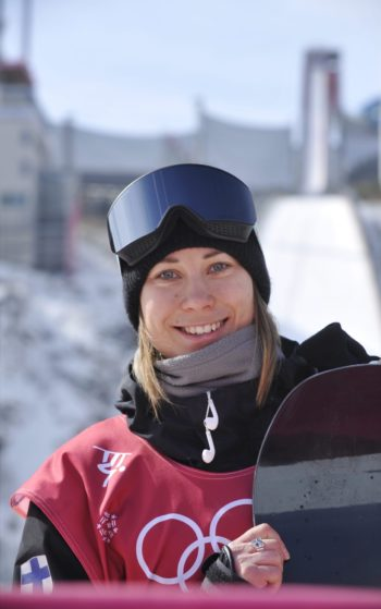 A woman dressed in sporty winter clothing holds a snowboard and smiles at the camera.
