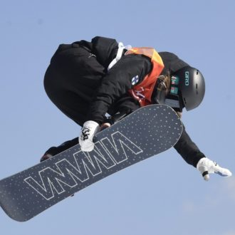 A woman on a snowboard is in the air, the sky visible behind her.