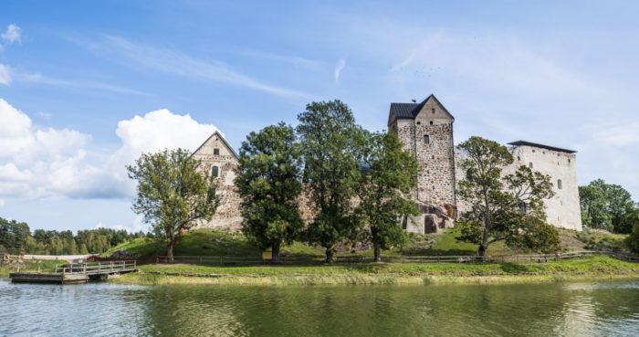 A cluster of medieval stone buildings stand by a body of water.