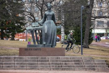 A statue of a woman holding an open book stands in a park while a man bikes past in the background.