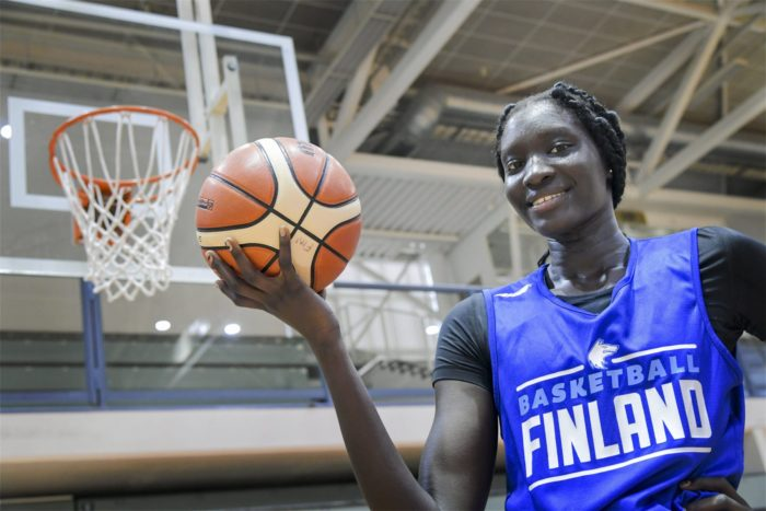 "A smiling young woman in a shirt with the word ""Finland"" on it holds a basketball in her upturned palm."