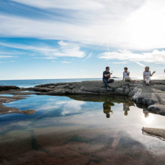 Four people sit on a large smooth rock by the ocean, their glasses raised in a toast.