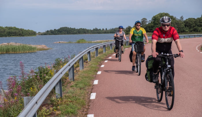Three people bike along a coastal road.