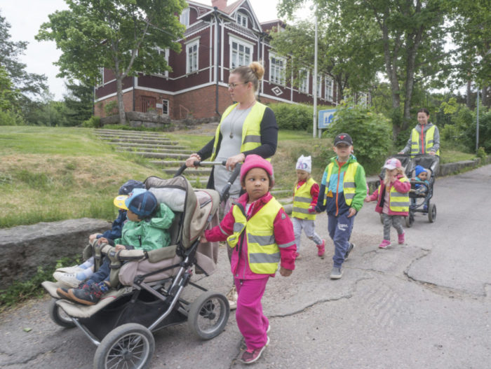 A group of daycare kids walk down the street in reflective vests with their caretakers.