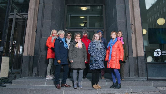 Nine women stand in front of a stone building in cold weather in Helsinki.