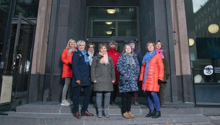 Nove mulheres estão em frente a um prédio de pedra em um clima frio em Helsinque.
