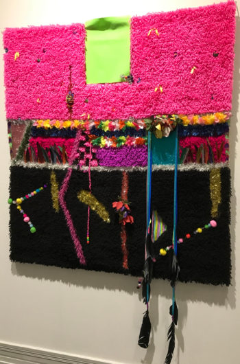 Uma tapeçaria de parede em rosa e outras cores vivas, contém também fileiras de contas e várias penas penduradas em cordões presos a ela.