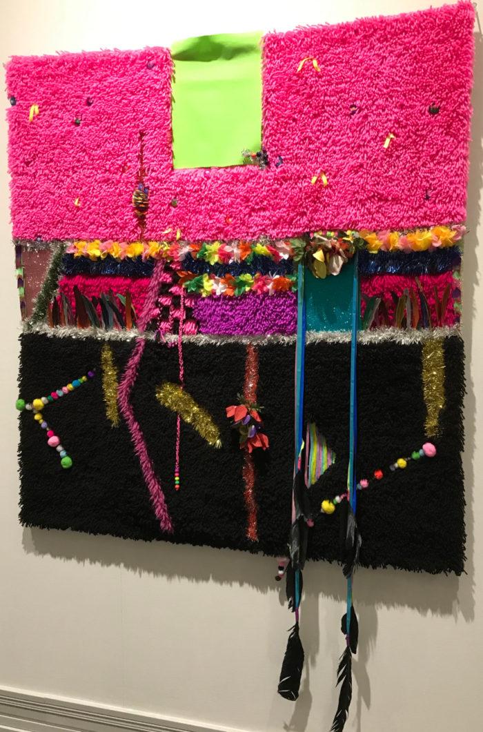 Настенный ворсовый ковер с розовым и другими яркими цветами, а также с рядами бусин и несколькими перьями, свисающими на веревочках, привязанных к ковру.