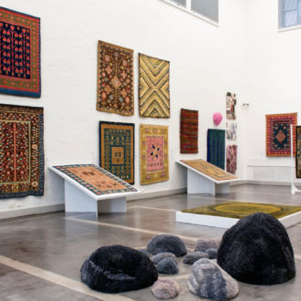 In a spacious museum gallery, rugs and tapestries are hanging on the walls.