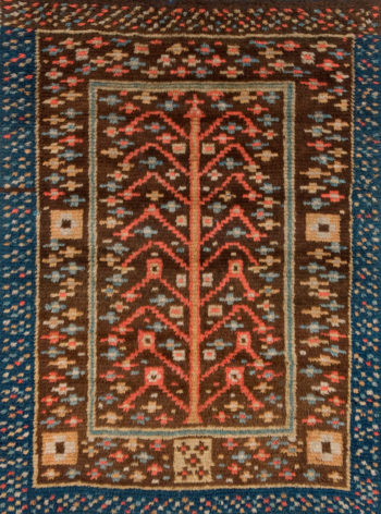 A tapestry shows a stylised tree made out of simple lines, surrounded by a border with several repeating patterns.
